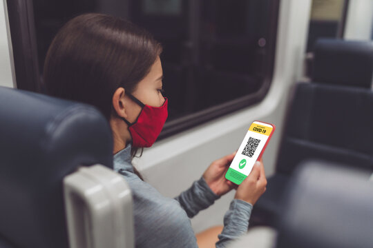 Vaccine passport app for public transport woman passenger using mobile phone online obligatory proof wearing face mask sitting in train or bus.