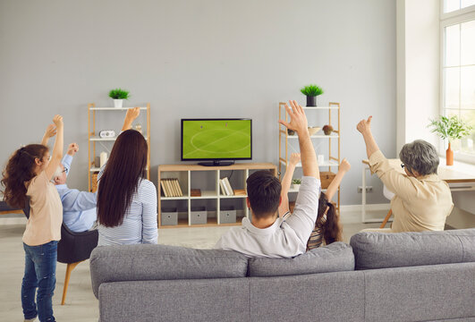 Multi generational family watching football on television. View from behind three generations sitting on sofa enjoying World Cup soccer match on LED LCD plasma TV screen in modern living room interior