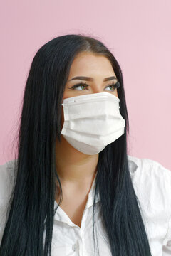 Girl with black hair and a mask on a pink background
