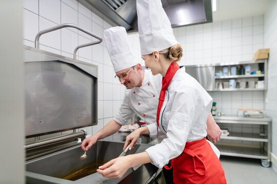 Chefs in large commercial kitchen cooking meals together stirring the sauce