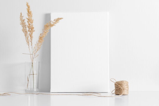 White canvas mockup with shadow and glass vase with reeds foliage branches on white table
