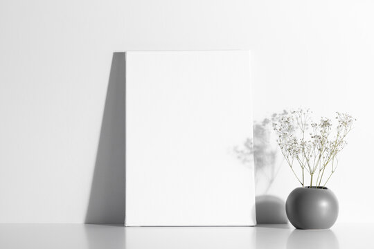 White canvas mockup with shadow and vase with gypsophila on white table