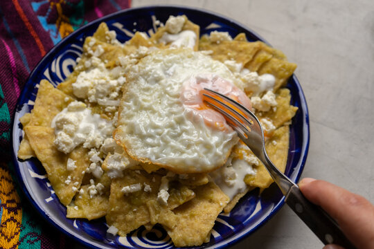 Mexican food. Green chilaquiles with cheese and fried egg on grey background