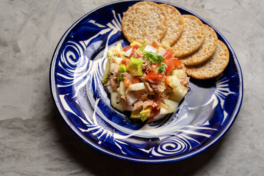 Tuna salad with avocado and cucumber on grey background