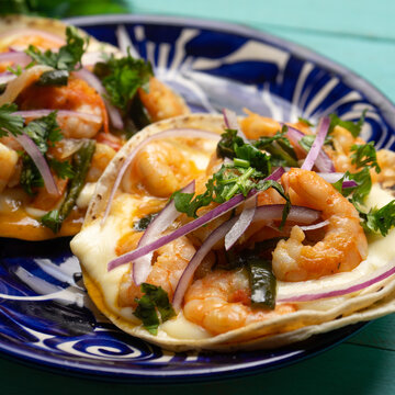 Mexican food. Shrimp tacos with melted cheese and poblano pepper called gobernador on turquoise background.