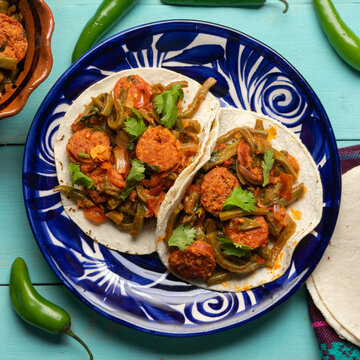 Mexican food. Chorizo and nopales tacos on turquoise background