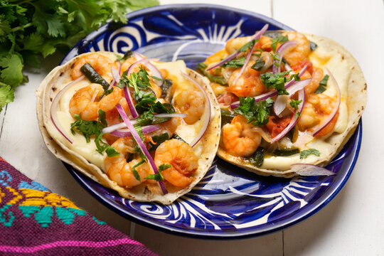 Mexican food. Shrimp tacos with melted cheese and poblano pepper called gobernador on white background.