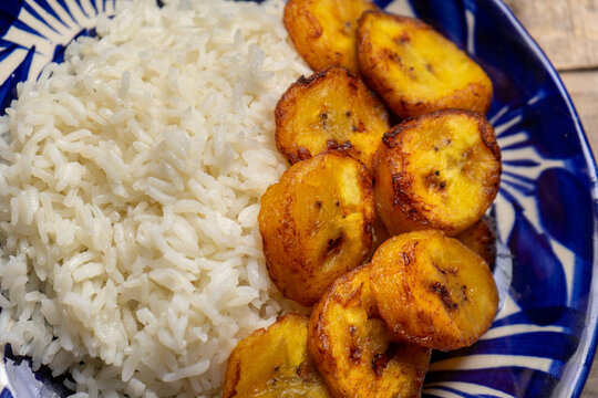 Rice and fried banana also called cuban style on wooden background