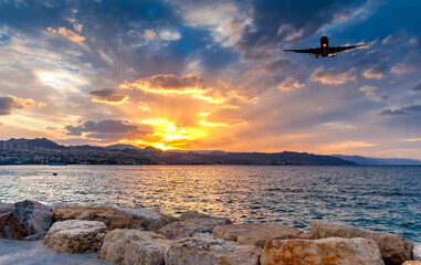 Dramatic sunset above mountains and Red Sea  and landing airplane