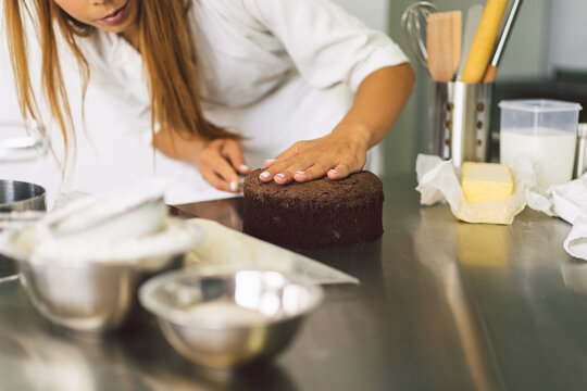 Confectioner girl is preparing a cake biscuit with white cream and chocolate. Cooking cakes.