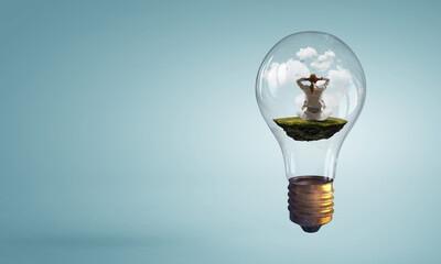 Business woman doing yoga in lotus pose inside light bulb