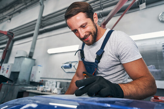 Automotive repairman checking quality of grinded surface