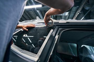 Repairman isolating windows of car with insulating tape