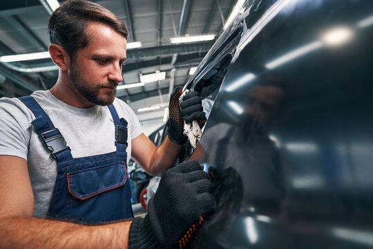 Auto mechanic using vice grip on car external detail