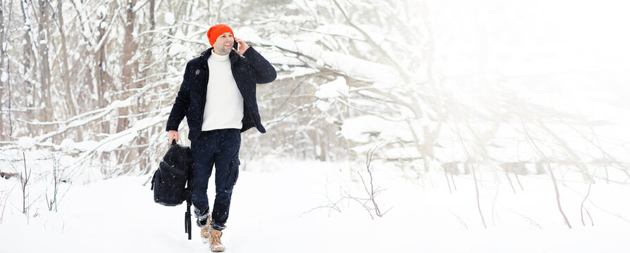 A man in the winter in the forest. A tourist with a backpack goes through the woods in winter. Winter ascent.