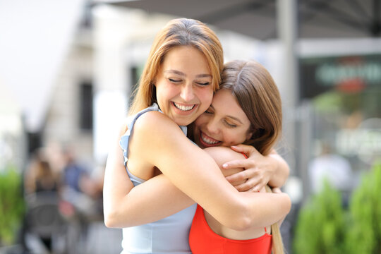 Happy friends hugging and laughing in the street