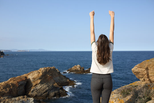 Excited woman raising arms in the coast