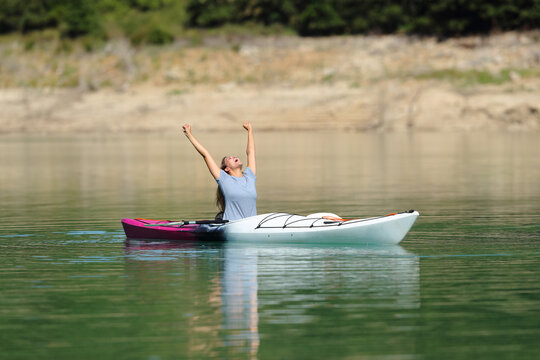 Happy woman in a kayak raising arms celebrating vacation