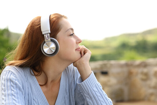Woman listening to music on headphones outdoors