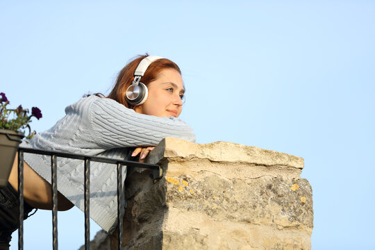 Woman contemplating from balcony listening to music