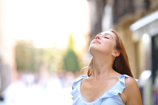 Woman is breathing fresh air in the street