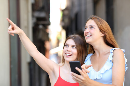 Happy women using phone and pointing in the street