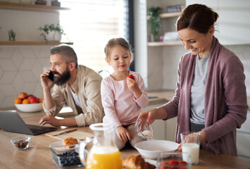 Obraz Family with small daughter indoors in kitchen, everyday life and home office with child concept. - fototapety do salonu