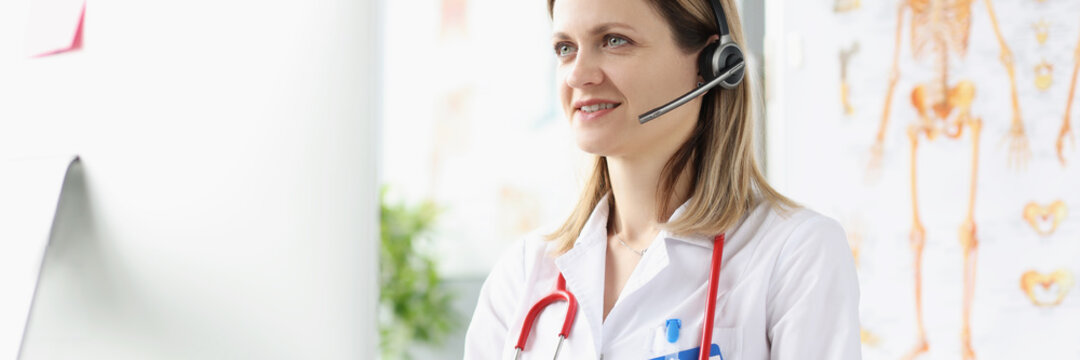 Smiling female doctor consultant in headphones is providing medical assistance remotely