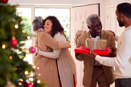 Adult Children Greeting Senior Parents As They Arrive With Presents To Celebrate Christmas
