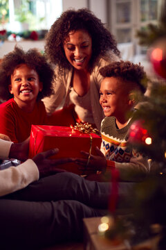 Family Exchanging And Opening Gifts Around Christmas Tree At Home