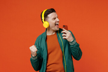 Fun satisfied young brunet man 20s wears red t-shirt green jacket listen to yellow headset...