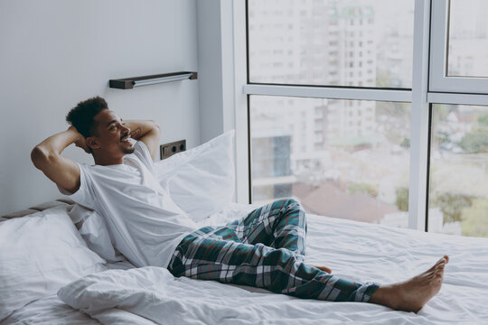 Full body profile young african american man in nightwerar hold hand behind neck lying in bed rest relax spend time in bedroom lounge home in own room house wake up dream be lost in reverie good day