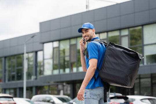 Cheerful muslim courier with thermo backpack talking on cellphone on urban street