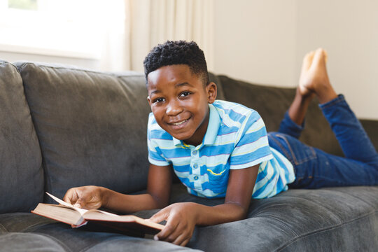 Portrait of smiling african american boy reading book and lying on couch in living room