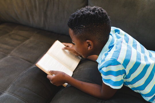 African american boy reading book and lying on couch in living room