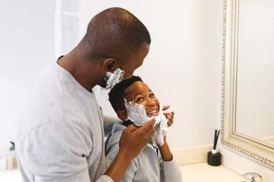 African american father with son having fun with shaving foam in bathroom