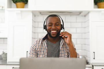 Laughing african american man sitting in kitchen making video call using laptop and headset