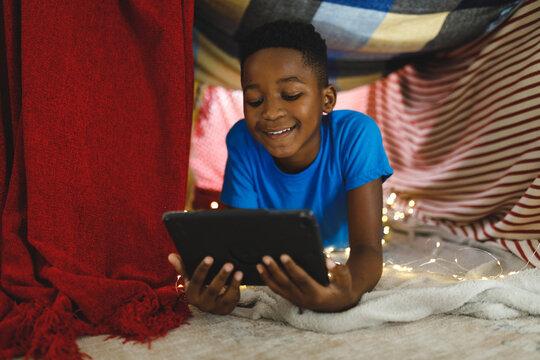 Happy african american boy lying in blanket fort, using tablet
