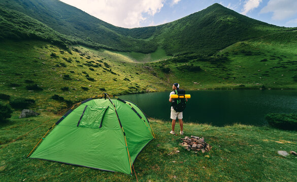 A male tourist with a backpack and a rubber mat stands near a tent by the lake. A young hiker at the foot of the green mountains. Travel, vacation, tourism.