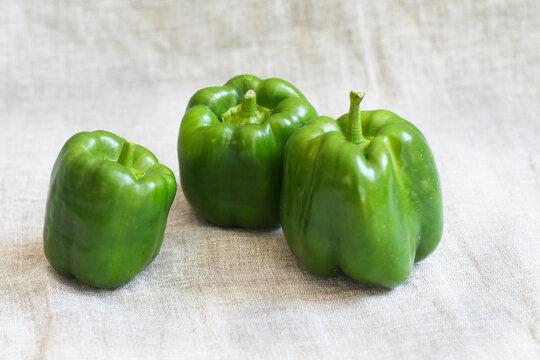 Drei grüne Paprikas - ein wertvolles Gemüse für die tägliche Ernährung, reich an Vitaminen und Ballaststoffen