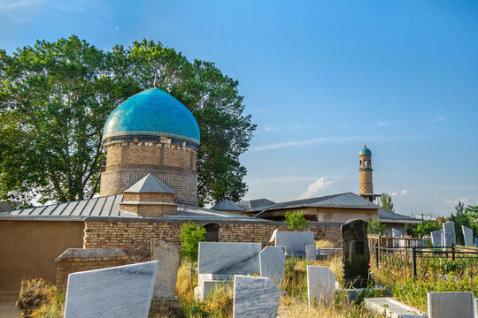 Building of mausoleum of Khoja Abdi Darun with blue dome. Founded in XII. In foreground are grave slabs. In distance you can see minaret, which is also part of complex. Shot in Samarkand, Uzbekistan
