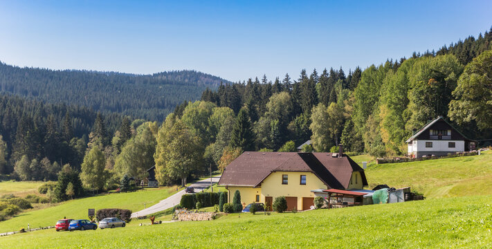 Panorama of a house in the landscape of the Sumava mountains national park, Czech Republic