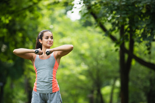 young sportswoman looking away while working out with dumbbells in park