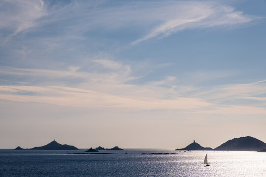 A sailing yacht and superyacht pass the genoese tower and lighthouse of Les Iles Sanguinaires near Ajaccio in Corsica silhouetted against a blue afternoon sky with sunshine lighting up the Mediterrane