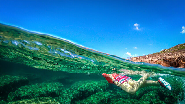 Split underwater view of a woman swimming in the blue sea  over a rocky seabed in Sardinia,
