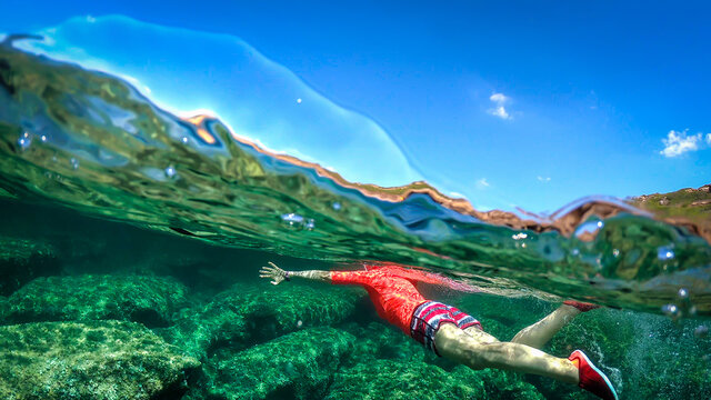 Split underwater view of a woman swimming in the blue sea in Sardinia