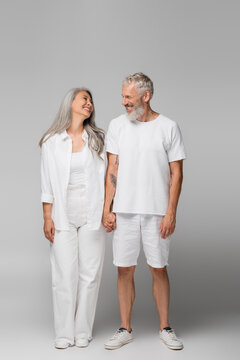 full length of cheerful interracial and mature couple holding hands on grey