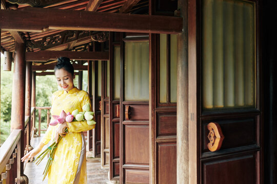 Beautiful smiling young woman in ao dai dress standing on porch with bunch of lotus flowers