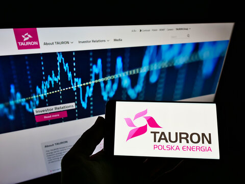 STUTTGART, GERMANY - Jun 03, 2021: Person holding mobile phone with logo of Tauron Polska Energia SA on screen in front of web page.