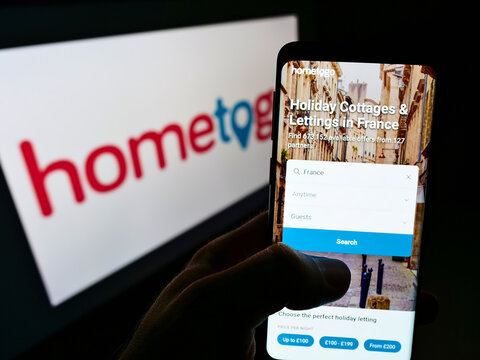 STUTTGART, GERMANY - Jun 07, 2021: Person holding cellphone with webpage of search engine HomeToGo GmbH on screen with logo.